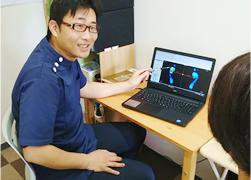すこやか整骨院 松山砥部院:足圧測定器の検査結果を見ながら説明している写真